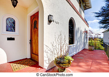 Spanish style white house with red porch and front door.