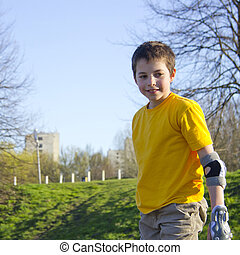 smiling teenage boy in roller-blading protection kit in a...