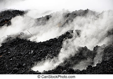 Charcoal pile burning in the outdoors, Romania