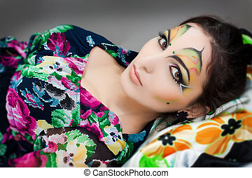young happy girl lying with beautiful make up on her face