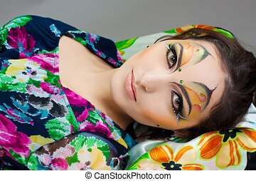 young girl lying with beautiful make up on her face
