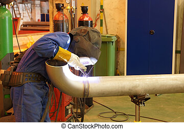 Welder - Factory worker welding  a metal pipe