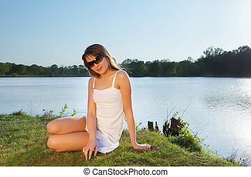young woman in sunglasses on water background