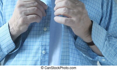 man buttons shirt - a businessman buttons up his dress shirt...