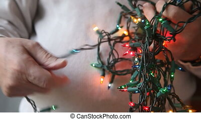 untangling colored Christmas lights - a man tries to...