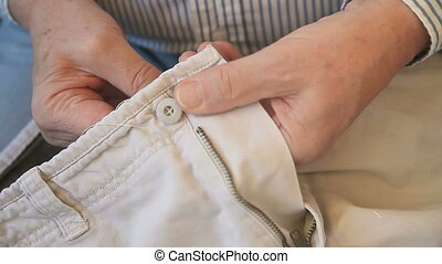 man sewing button - a man sews a button back onto a pair of...