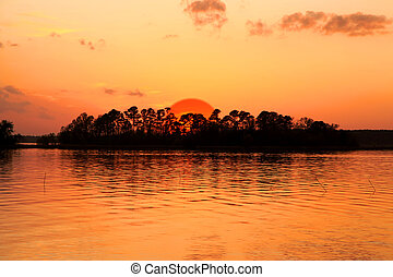 Sun set - Bright orange sky with Sun set over island