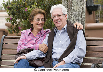 Happy Senior Couple Sitting On Park Bench