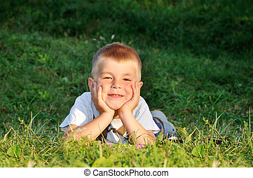 happy little boy laying on the grass in nature looking at camera