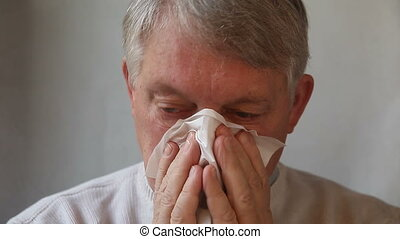man blows his nose - a senior man blows his nose very...