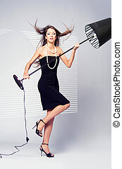 girl and a floor lamp - scandalous woman in a black dress...