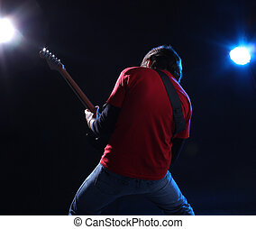 Musician playing electric guitar on stage