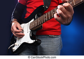 Detail of a musician playing a black electric guitar