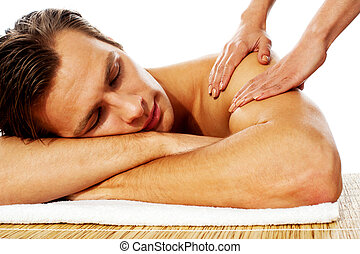 Attractive man having massage in a spa center