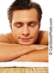 Attractive man resting with closed eyes at spa. Front view,...