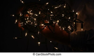 string of Christmas lights - profile view of man untangling...