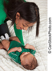 ethnic mother playing with her baby boy son on bed -...
