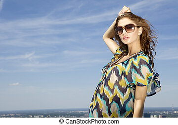 beautiful girl in sunglasses on background blue sky -...