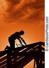 Stormy sunset on construction site with carpenter working