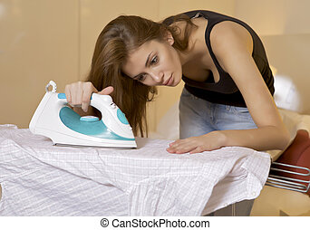 young woman ironing on ironing board