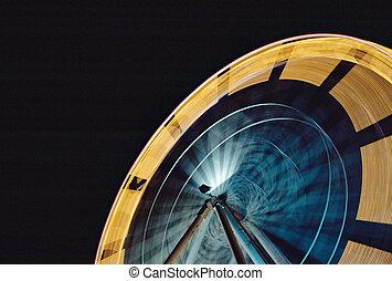 Ferris wheel carousel in fun fair at night - Yellow and blue...