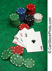 Four aces with gambling chips over green felt