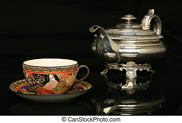 Silver teapot and an antique chinese cup of tea More in...