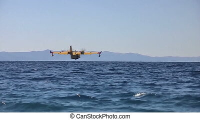 Airplane landing at sea close up - Yellow airplane landing...