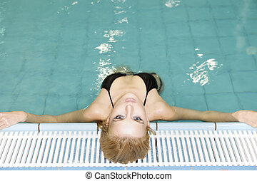 beautiful young woman standing in a swimming pool - Portrait...