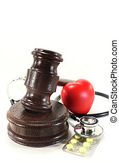 medical law - judges gavel with stethoscope and pills