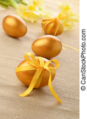 Easter eggs - Golden Easter eggs with bows on over floral...