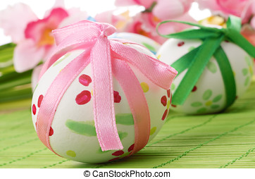 Easter eggs with bows over green background