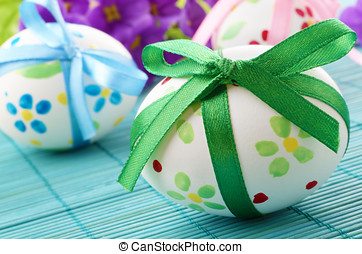 Easter eggs with bows over blue background
