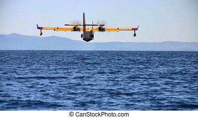 Firefighter airplane landing at sea - Yellow fire fighter...