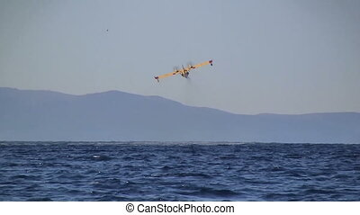 Yellow airplane flying over blue Adriatic sea