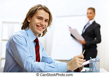 Young businessman at work in office - Young smiling happy...