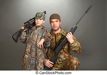 the boy and the adult man in a camouflage with rifles nearby...