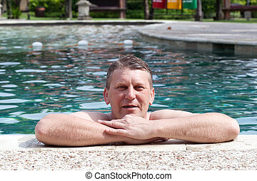 mature smiling man in the pool in tropical hotel