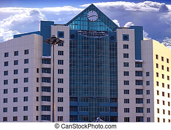 facade of modern building with a clock in blue and white tones on a background bright sky