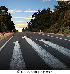 Empty countryside road with white arrow
