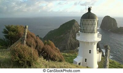 Cape Brett lighthouse with Piercy Island in the distance,...