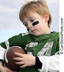 Little boy holding a football, American Football eye black