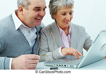 Tech for senior - Cheerful senior couple using a laptop