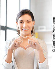 happy woman making heart gesture - bright picture of happy...