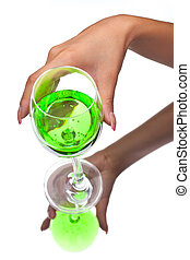 Hand holding a glass of green transparent liquid