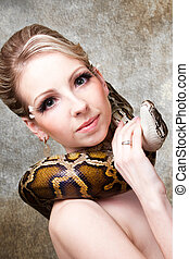 Attractive nude blond woman with python on grey  background