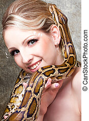 Attractive nude blond woman with python on grey