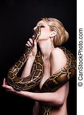Kiss of attractive nude blond woman with python on black