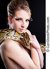 attractive nude blond woman with python on black background