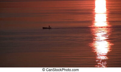 Small boat on sea at sunset